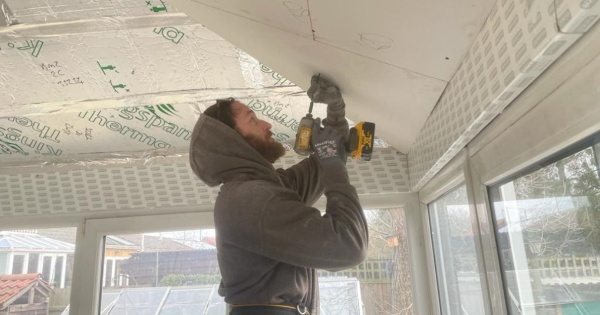A man cutting the insulated plasterboard for a conservary roof conversion 2