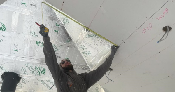 A man measuring the insulated plasterboard for a conservatory roof conversion 2