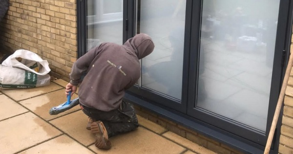 Construction worker cleaning conservatory windows after a conservatory conversion 2 (1)