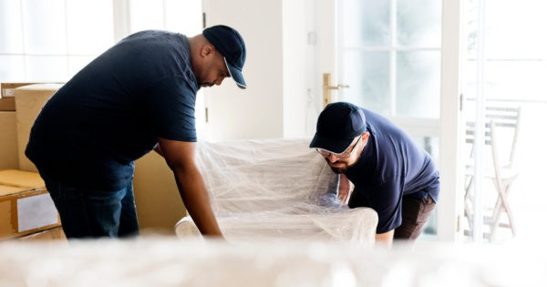 Two men protecting and moving furniture before a conservatory roof conversion 2