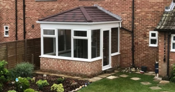 A small conservatory with a solid conservatory roof