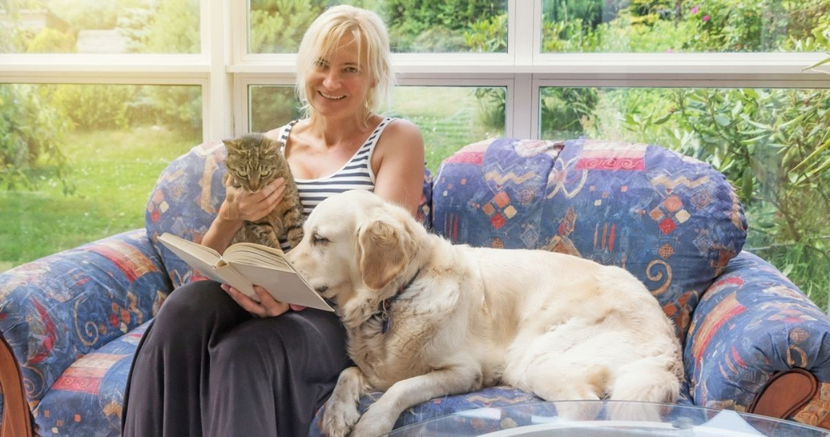 Woman reading in conservatory with her pets