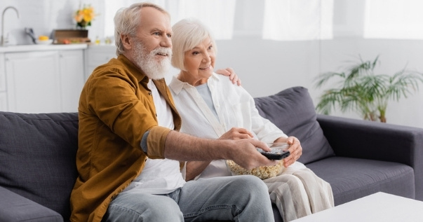 Mature couple watching a movie in their conservatory after they replaced their conservatory roof with a guardian roof. (1)