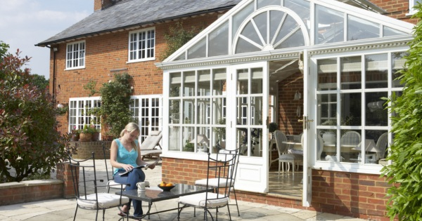woman outside a conservatory room with a conservatory roof by Projects 4 Roofing