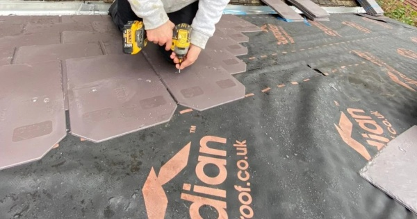 Conservatory roofing installer installing roofing tiles on a guardian roof