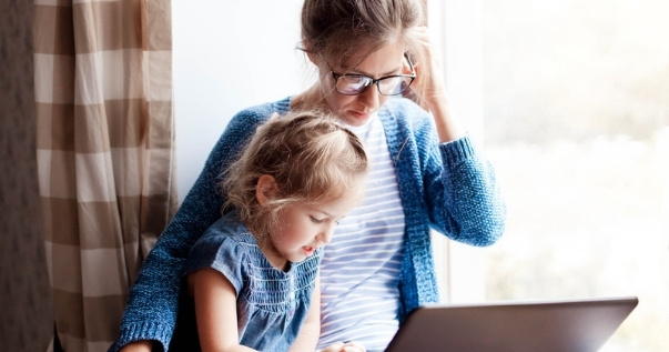 Mom working from home with her daughter inside their converted conservatory